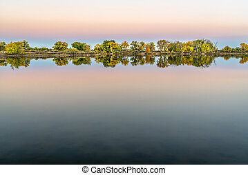 dusk over a calm lake with fall colors