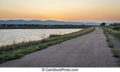 dusk over bike trail with Rocky Mountains in background,