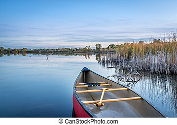 dusk over calm lake with a canoe