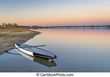 dusk over lake with a paddleboard