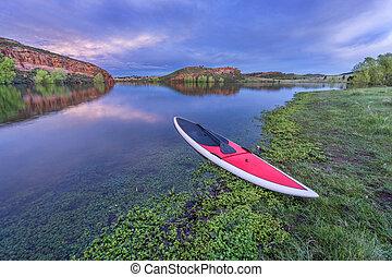 dusk over lake with paddleboard