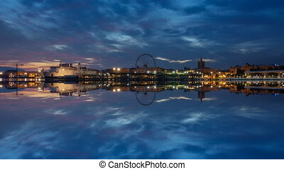 Dusk over Malaga city skyline and reflection - Time lapse at...