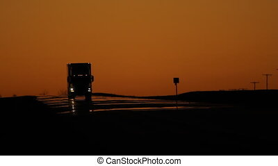Dusk traffic with trucks. - Dusk traffic with orange sky....