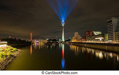 Dusseldorf skyline at night with light beaming from the rheinturm