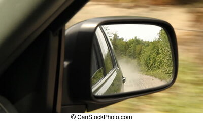 Dust in rearview mirror. - Driving an SUV on a dusty road....