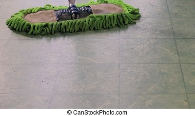 Dust mop mopping floor - green dust mop mopping across a...