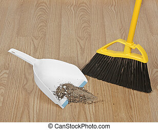 Dust Pan and Broom - Broom sweeping up dirt into dust pan on...