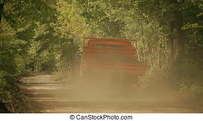 Dust Trailing Truck Running on Gravel Wood Road
