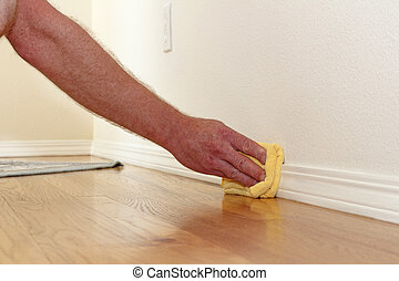 Dusting a Baseboard - Male caucasian hand and arm seen...