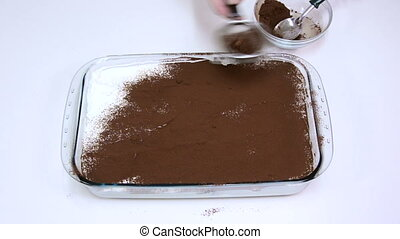 Dusting tiramisu by cocoa - Housewife dusting top layer of...