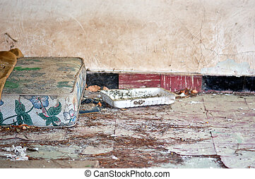 Dusty mattress and blanket on the tilled floor of an abandoned house.