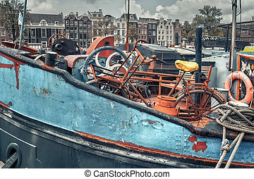 Dutch blue ship in Amsterdam with a rusty bicycle on it