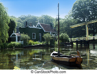 dutch bridge and water with wooden boat