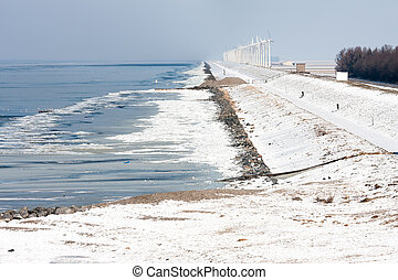 Dutch coast with wind turbines in wintertime and frozen sea