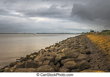 dutch coastline with rocks for dike protection and dark...