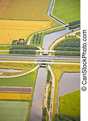 Dutch farm landscape with infrastructure road and canal