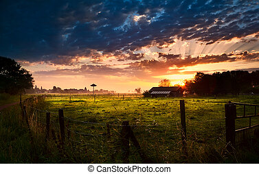 Dutch farmhouse at sunrise - farmhouse with fence at summer...