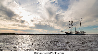 Dutch harbor of Urk with sunset and sailing ship