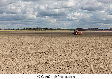 Dutch landscape with tractor in plowed field in early spring