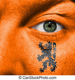 Dutch Lion painted on orange face with green eye to show Netherlands support in sport matches