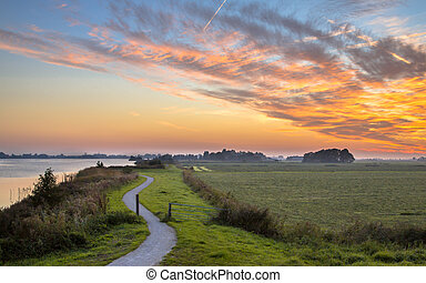 Dutch Polder landscape with winding cycling track along river under beautiful sunset