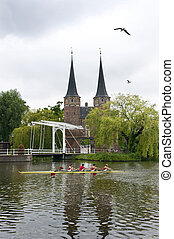 Dutch Rowing - A rowing team in a coxed four rowing past a...