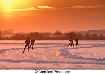 Dutch speed skaters are back lit by setting sun