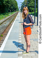 Dutch teenage girl standing at station waiting on train