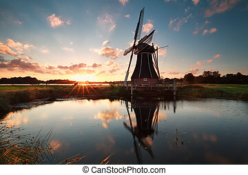 Dutch windmill by lake at sun down, Netherlands