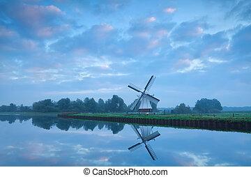Dutch windmill close to river during calm sunrise