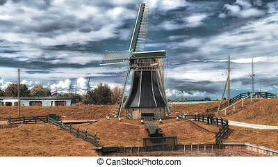 Dutch windmill in a landscape with clouds in the sky