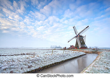 Dutch windmill in winter over blue sky, Holland