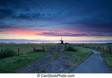 Dutch windmill on meadow at sunrise