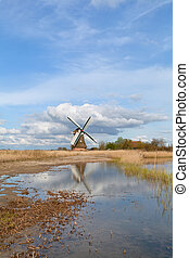 Dutch windmill over blue sky and river