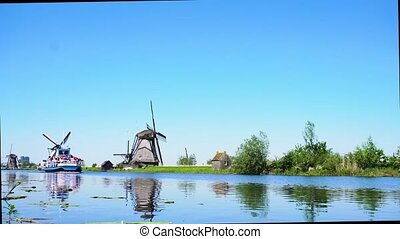 dutch windmill over river waters - dutch windmills with boat...