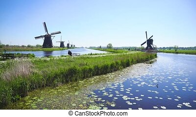 dutch windmill over river waters - Kinderdijk heritage site...