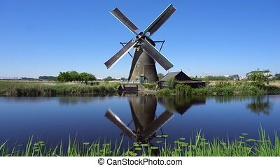 dutch windmill over river waters - one traditional dutch...