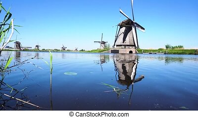 dutch windmill over river waters - traditional dutch...