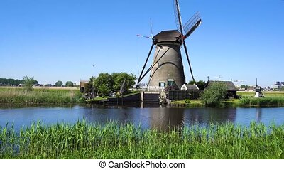 dutch windmill over river waters - view of traditional dutch...