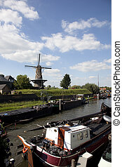 dutch windmill with old traditional ship in the front
