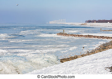 Dutch winter landscape with frozen sea and drifting ice.
