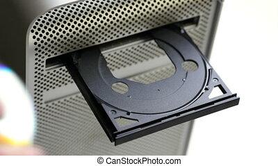 dvd - man inserting dvd in computer. 30p
