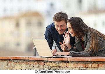 dvojice, počítač na klín, video, venku, hovor, obout si