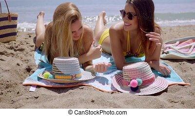 dwa, dziewczę, leżący, słońce garbarstwo, na, niejaki, plaża