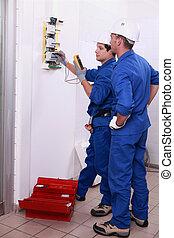dwa, elektromonterzy, kontrolowanie, elektryczny, dostarczcie energii elektrycznej dostarczają