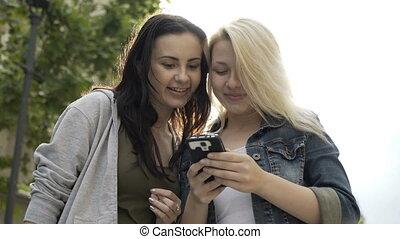 dwa, młode dziewczyny, śmiech, i, zwijanie, touchscreen, od, smartphone, przeglądnięcie, coś, zabawny, na, internet, towarzyski, media