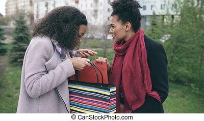 dwa, młody, afrykańscy amerykańscy kobiety, dzielenie, ich, nowy, nabycia, w, shoppping, mnóstwo, z, każdy, inny., pociągający, dziewczyny, mówiąc, i, uśmiechanie się, po, odwiedzając, mall, zbyt