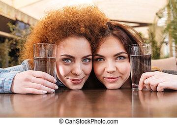 dwa, piękni kobiety, dzierżawa okulary, od, woda, posiedzenie, w, kawiarnia