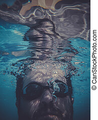dwimmer, man swimming underwater in a pool
