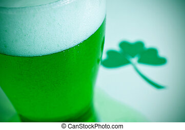 closeup of a glass with dyed green beer and a three-leaved shamrock in the background, for saint patricks day